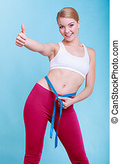 Diet. Fitness woman fit girl with measure tape measuring her waist