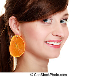 Diet. Girl with earrings of orange fruit isolated