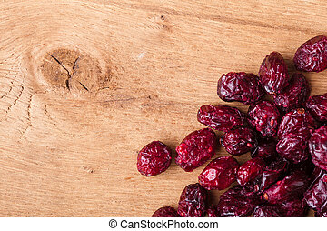 Healthy food organic nutrition. Border frame of dried cranberries cranberry fruit on wooden background