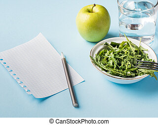 Diet leaves salad green Apple a glass of water on blue background. Label note