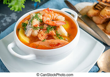 Diet soup of seafood and fish of different varieties in a white soup plate. Close up