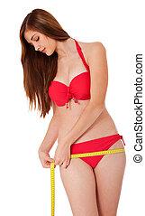 Diet - Attractive woman in bikini using measuring tape....