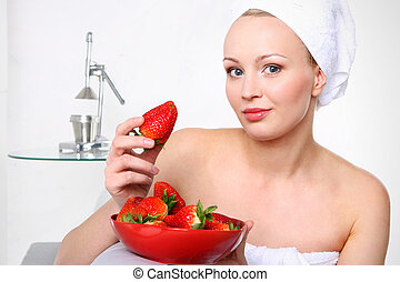 Attractive girl with a bowl of ripe strawberries relaxes in the living room.
