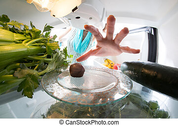 Diet struggle: A hand grabbing a tiny candy from the open refrigerator full of greens.
