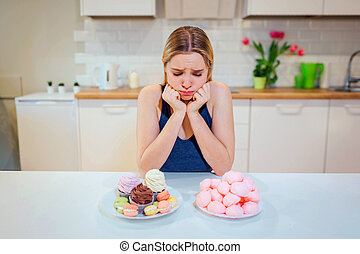 Diet struggle. Young sad woman in blue T-shirt chooses between fresh fruit vegetables or sweets while looking at them in the kitchen. Healthy and unhealthy food. Dieting