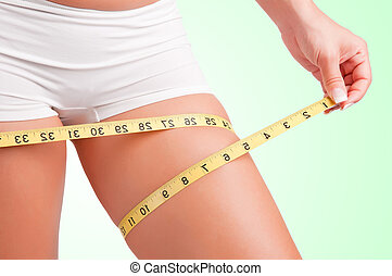 Diet Time - Woman measuring her thigh with a yellow...