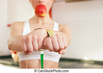 Woman handcuffed by a tape measure and gagged by an apple - symbol for eating disorder