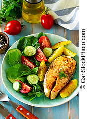 Dietary and healthy nutrition. Grilled salmon steak and baked potatoes with fresh vegetable salad on a wooden table.