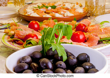 Dietary dishes served at the table, with salmon, tomatoes, shrimp, arugula and olives