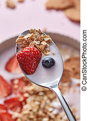 Dietary homemade natural breakfast with fresh organic ingredients - berries, granola, nuts and milk in a spoon above the bowl of food on a pink.