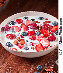 Dietary homemade natural breakfast with fresh organic ingredients - berries, granola, nuts and milk in a white bowl on a wooden table.