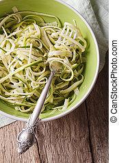 Dietary zucchini pasta in a bowl closeup. vertical top view...
