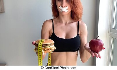 Dieting concept, beautiful young woman choosing between healthy food and junk food.
