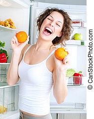 dieting, concept., skratta, ung kvinna, äta, rå frukt