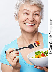 Elderly woman with salad on white background
