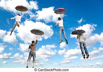 dietro, volare, quattro, amici, con, ombrelli, bianco, lanuginoso, nubi, in, cielo blu, collage