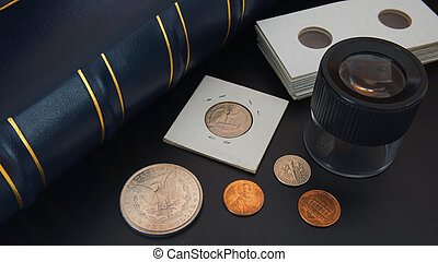 Different American coins on black table with magnifying glass, numismatic supplies and album for coins - Numismatic scene
