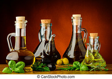 different bottles of infused olive oil with fresh green ...