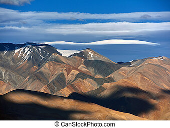 Different bright colors of the mountain valley, alternating black and orange strata of the sedimentary rocks, white sky with stripes of white clouds.