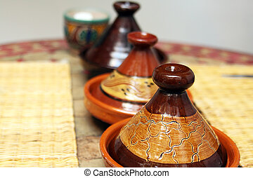 Different ceramic tajines with food on the table