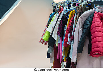 Different clothes on hangers in the professional photostudio