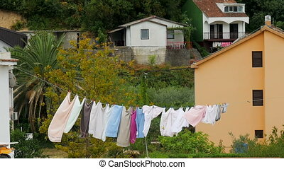 different colored underwear drying outside on the roof in...