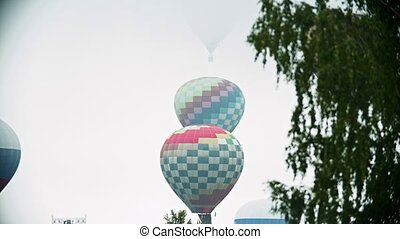Different colorful air balloons taking off over the field on...