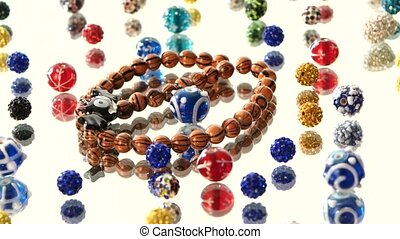 Different colorful beads on white background, cam moves to the left, rotation