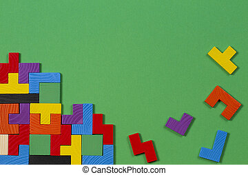 Different colorful shapes wooden blocks on green background. Top view