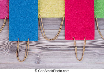 Different colors gift bags on wooden background.