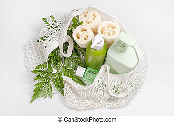 Different containers for lotion, shampoo, conditioner or liquid soap in eco bag. Loofah or luffa washcloth, vegetable sponge, alternative to plastic, zero waste, eco friendly. Natural beauty products