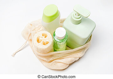 Different containers for shampoo, conditioner, tonic, liquid soap in eco bag. Loofah or luffa washcloth, vegetable sponge, alternative to plastic, zero waste, eco friendly. Natural beauty products