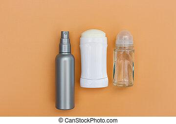 Different deodorants on beige background. Top view.