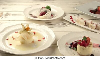 Different desserts on plates. Small cakes and berries. Creme...