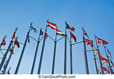 different flags on background of blue sky