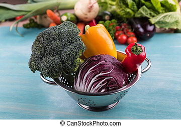 different fresh seasonal vegetables in colander on wooden table background