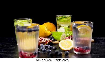 Different fruits and berries on a wooden board next to four glasses of detox water
