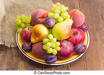 Different fruits on the big yellow dish on rustic table
