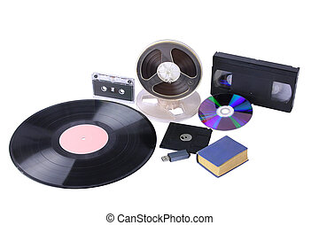 """Different mediums: little blue book, magnetic tape bobbins, audio cassette, video cassette, 3,5"""" diskette, vinil disk, USB flash drive, compact disk. They are isolated over white."""