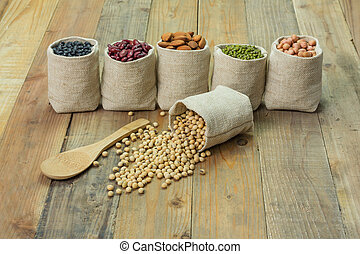 Different kinds of beans in sacks bag, focus on scattered soy beans