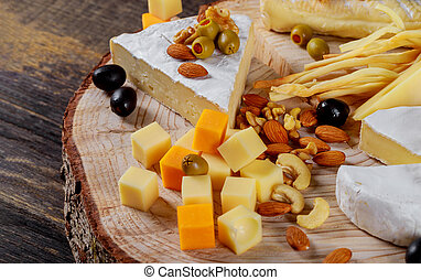Different kinds of cheese, olives and assorted nuts wood background