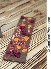 different kinds of chocolate with dried fruits on a wooden board