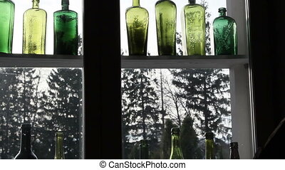Different kinds of colored bottles on the window