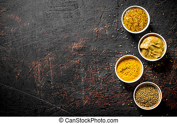 Different kinds of mustard in the bowls.