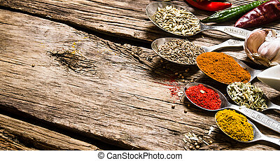 Different kinds of spices in spoons. On wooden background.