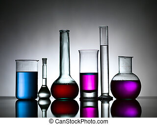 lateral view of different sizes and shapes of laboratory glassware, filled with differently colored substances against a gradient grey background laying on a reflective surface
