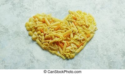 Different macaroni laid in shape of heart - From above view...
