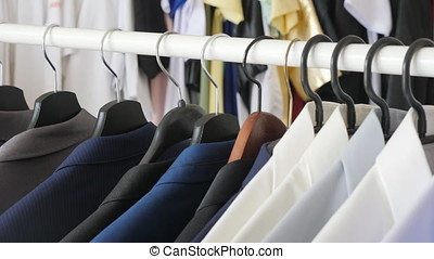 Different male business suits and shirts on hanger in a...