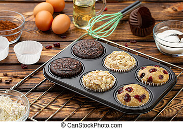 Different Muffins in bakeware or muffin pan on broun wooden...