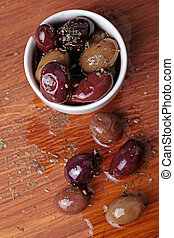 different olives in white bowl on wooden board
